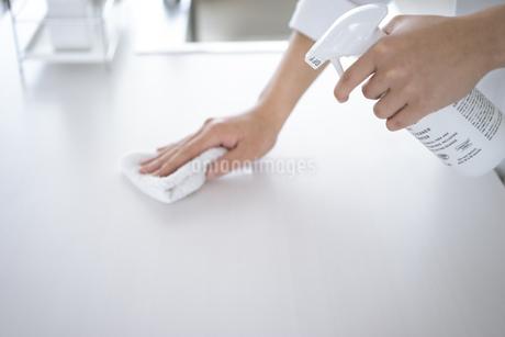 除菌スプレーで拭き掃除をする女性の手元の写真素材 [FYI04312121]