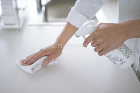 除菌スプレーで拭き掃除をする女性の手元の写真素材 [FYI04312122]