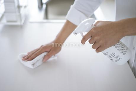 除菌スプレーで拭き掃除をする女性の手元の写真素材 [FYI04312123]