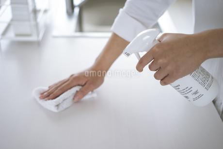 除菌スプレーで拭き掃除をする女性の手元の写真素材 [FYI04312124]