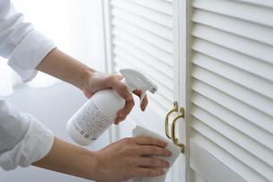 除菌スプレーで拭き掃除をする女性の手元の写真素材 [FYI04312125]