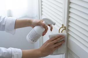 除菌スプレーで拭き掃除をする女性の手元の写真素材 [FYI04312127]