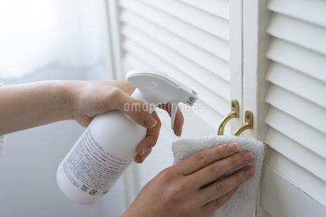 除菌スプレーで拭き掃除をする女性の手元の写真素材 [FYI04312128]