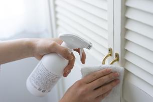 除菌スプレーで拭き掃除をする女性の手元の写真素材 [FYI04312129]