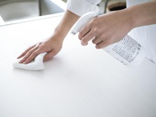 除菌スプレーで拭き掃除をする女性の手元の写真素材 [FYI04312136]