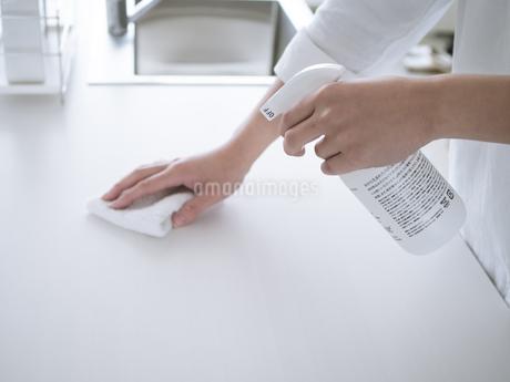 除菌スプレーで拭き掃除をする女性の手元の写真素材 [FYI04312137]