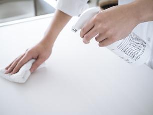 除菌スプレーで拭き掃除をする女性の手元の写真素材 [FYI04312140]