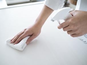 除菌スプレーで拭き掃除をする女性の手元の写真素材 [FYI04312144]