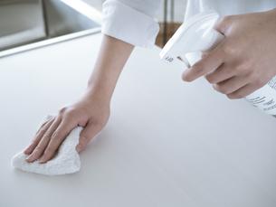 除菌スプレーで拭き掃除をする女性の手元の写真素材 [FYI04312148]