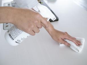 除菌スプレーで拭き掃除をする女性の手元の写真素材 [FYI04312152]