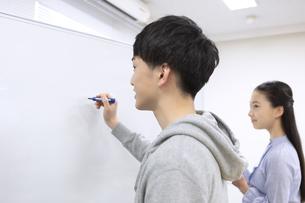 ホワイトボードに記入する男子学生の写真素材 [FYI04312747]