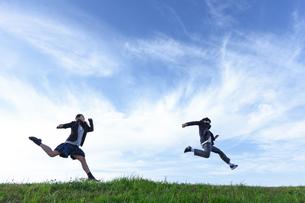 芝生を走る女子学生と男子学生の写真素材 [FYI04312861]