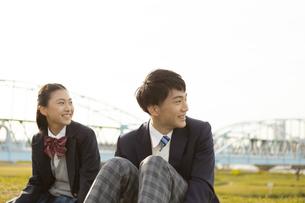 土手に座る女子学生と男子学生の写真素材 [FYI04312870]