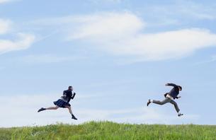 芝生を走る女子学生と男子学生の写真素材 [FYI04312884]