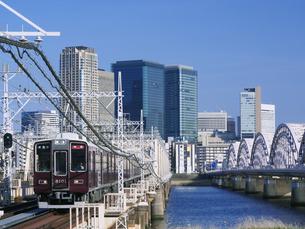淀川を渡る阪急電車と梅田のビル街の写真素材 [FYI04312942]