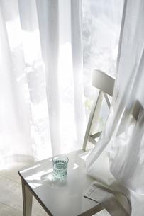 コップが置かれた窓際の椅子と白いカーテンの写真素材 [FYI04313169]