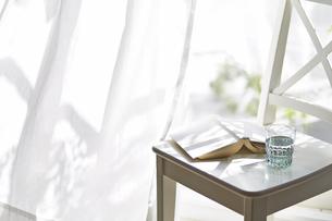 本とコップが置かれた窓際の椅子となびく白いカーテンの写真素材 [FYI04313170]