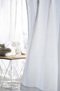 白いカーテンとタオルが積まれた窓際のテーブルの写真素材 [FYI04313171]