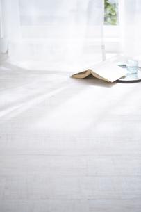 白い床と窓際の揺れるカーテンと本の写真素材 [FYI04313173]