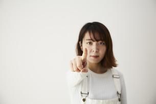 白い壁の前で指を指す女性の写真素材 [FYI04313189]