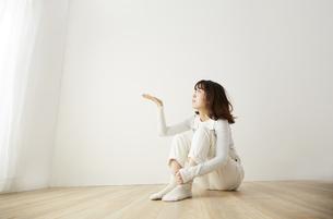 白い壁の前で座っている女性の写真素材 [FYI04313199]