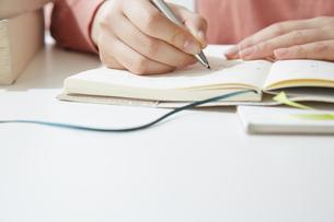 デスクで記帳する女性の手元の写真素材 [FYI04313219]