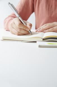 デスクで記帳する女性の手元の写真素材 [FYI04313220]