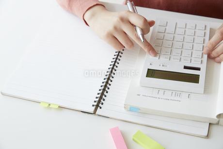 開いたノートの上で計算機を使って計算する女性の手元の写真素材 [FYI04313221]