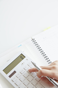 開いたノートの上で計算機を使って計算する女性の手元の写真素材 [FYI04313222]