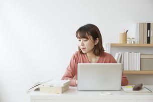参考書を見ながらパソコンの勉強をする女性の写真素材 [FYI04313223]