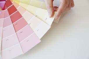 扇状に広がったカラーチップと女性の手の写真素材 [FYI04313227]