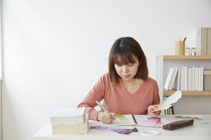 カラーチップを使って勉強をする女性の写真素材 [FYI04313228]
