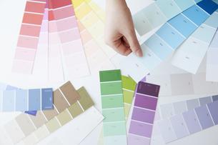 乱雑に広がったカラーチップと女性の手の写真素材 [FYI04313230]