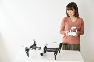 リモコンを持って机の上のドローンを見る女性の写真素材 [FYI04313232]