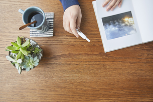 カフェで本を見るアイコスを持つ男性の手元の写真素材 [FYI04313244]