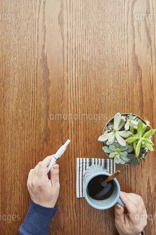 カフェでコーヒーカップとアイコスを持つ男性の手元の写真素材 [FYI04313245]