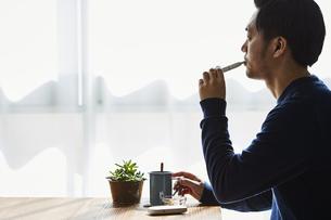 カフェでアイコスを吸う男性の写真素材 [FYI04313246]