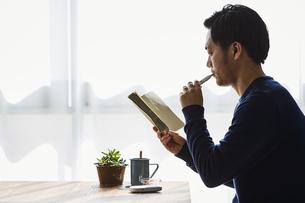 カフェで本を読みながらアイコスを吸う男性の写真素材 [FYI04313247]