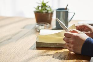 カフェでアイコスを持ち本を読む男性の手元の写真素材 [FYI04313249]