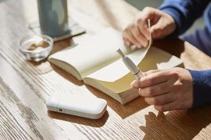 カフェでアイコスを持ち本を読む男性の手元の写真素材 [FYI04313251]