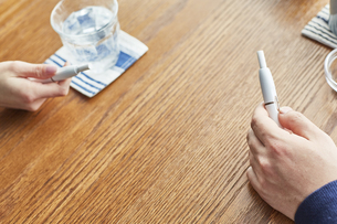 カフェでお茶をするアイコスを持った男女の手元の写真素材 [FYI04313252]