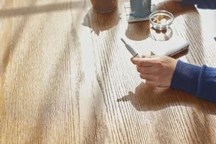 カフェでお茶をするアイコスを持った男性の手元の写真素材 [FYI04313253]