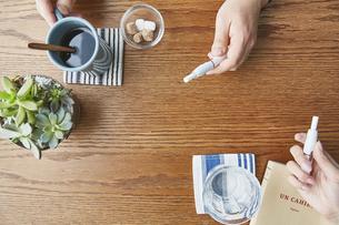 カフェでお茶をするアイコスを持った男女の手元の写真素材 [FYI04313254]