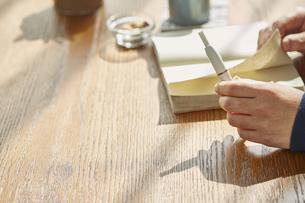 カフェでアイコスを持ち本を読む男性の手元の写真素材 [FYI04313256]