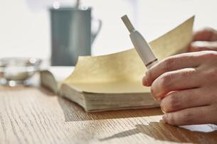カフェでアイコスを持ち本を読む男性の手元の写真素材 [FYI04313257]