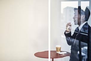 喫煙ルームでアイコスを吸うサラリーマンの写真素材 [FYI04313270]