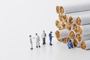 たばこを調査するミニチュアの作業員たちの写真素材 [FYI04313279]