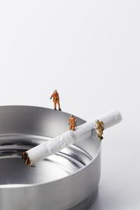 たばこの吸い殻とミニチュアの消防士の写真素材 [FYI04313287]