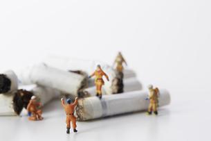 たばこの吸い殻とミニチュアの消防士の写真素材 [FYI04313293]