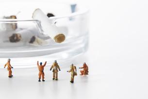 たばこの吸い殻とミニチュアの消防士の写真素材 [FYI04313294]